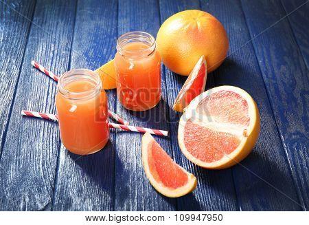 Grapefruit juice in bottles and fresh fruits on dark blue wooden background