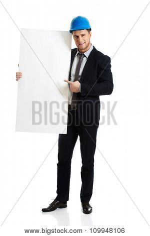 Handsome businessman in hard hat pointing on empty banner.