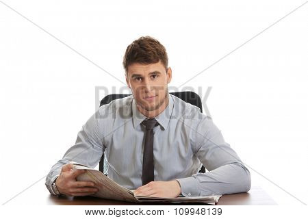 Happy businessman reading newspaper in the office.