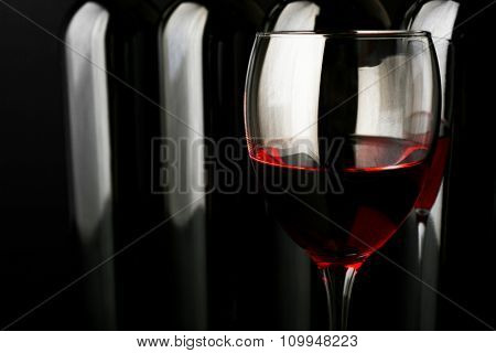 Red wine glass against bottles in a row on black background, close up