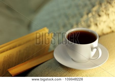 Cup of coffee with books on comfortable sofa, close up
