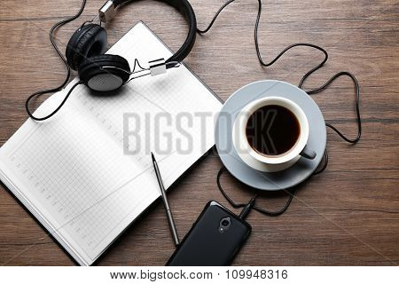 Headphones with papers and cup of coffee on wooden table