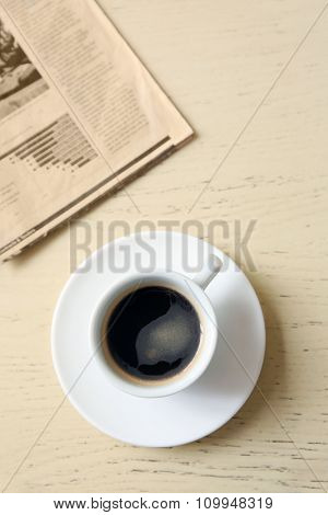 Cup of tasty coffee with newspaper on table