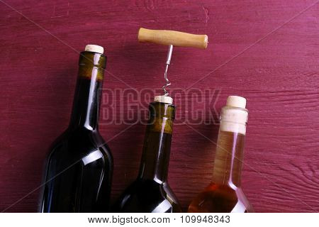Three bottle wine and corkscrew on purple wooden background