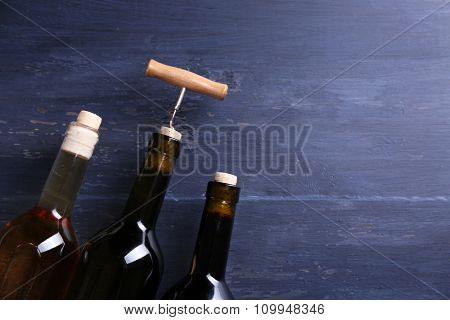 Three bottle wine and corkscrew on blue wooden background