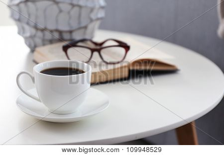 Cup of coffee with book on table in room