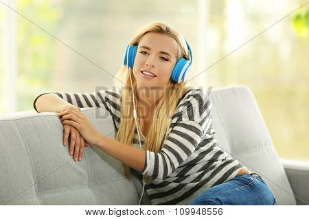 Young woman on a sofa listening to music