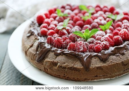 Cake with Chocolate Glaze and raspberries on wooden background