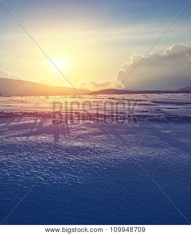 Beautiful winter landscape, bright yellow sunset light over mountains covered with clean white snow, amazing wintertime nature