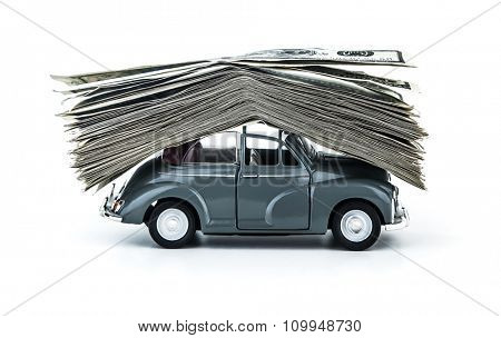 Side view on small decorative car model carries on itself a lot of cash isolated on white background, dollars of USA, credit for car concept