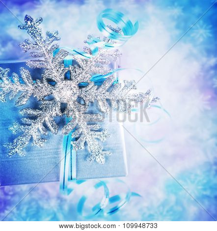 Beautiful Christmas present, elegant festive still life, gift box wrapped in silver paper decorated with shiny snowflake over blurry background