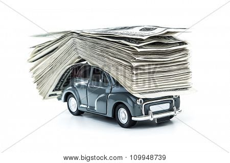 Small decorative car model carries on itself a lot of cash isolated on white background, dollars of USA, credit for car concept