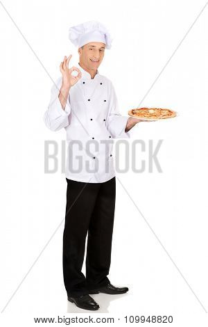 Chef baker with italian pizza on plate showing perfect sign.