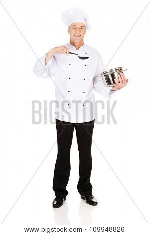 Restaurant chef holding steel pot and spoon