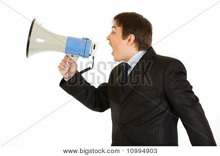 Frustrated young businessman yelling through megaphone