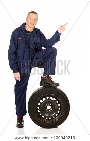 Car mechanic with leg on a tire pointing to the left.