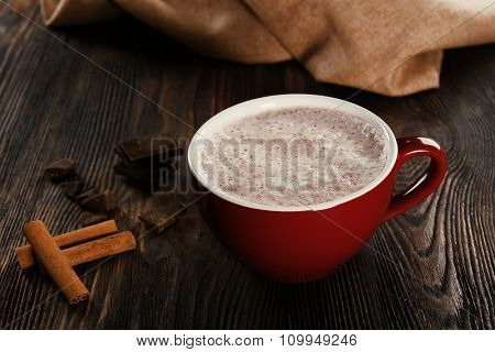 Cup of hot cacao with cinnamon and sweets on wooden background, close up