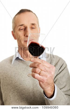 Smiling mature man tasting red wine.
