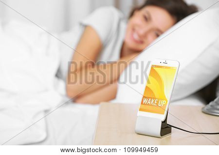 Beautiful young woman waking up with mobile alarm clock