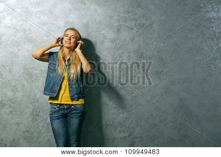 Young woman dancing and listening to music on grey wall background
