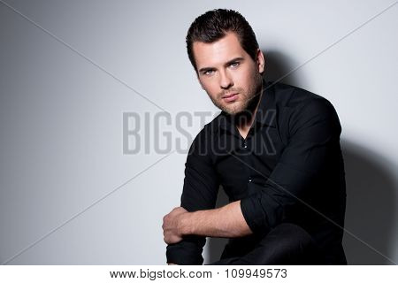 Fashion portrait of sexy young man in black shirt poses over wall with contrast shadows.