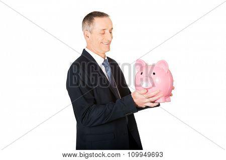 Smiling mature businessman with piggybank.