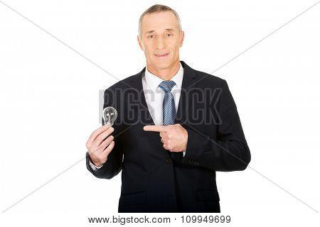 Mature businessman showing llight bulb