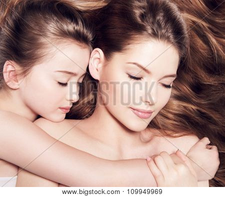 Beautiful young mother with a small daughter 8 years lying together with closed eyes