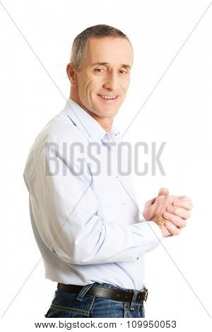 Smiling mature man with clenched hands.