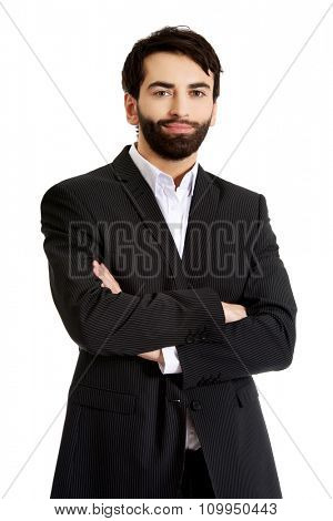 Smiling confident businessman with folded arms.