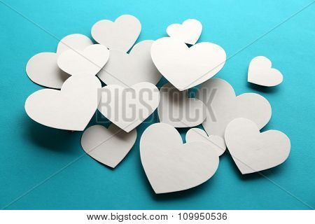 White paper hearts on blue background