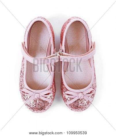Girl shiny pink shoes isolated on white background