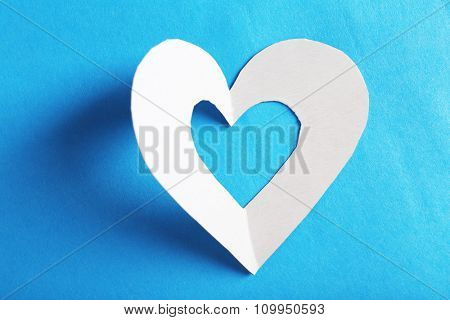 Cut out white paper heart on blue background