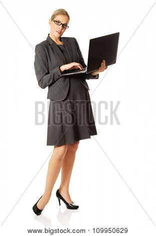Businesswoman standing and holding a laptop.