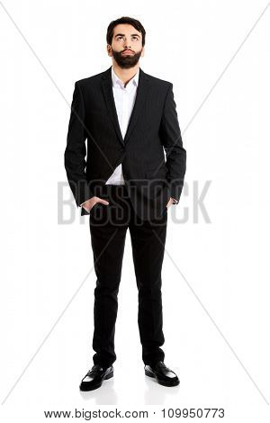 Handsome pensive businessman with hands in pockets.