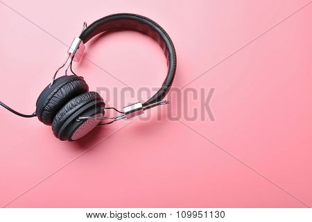 Black headphones on pink background