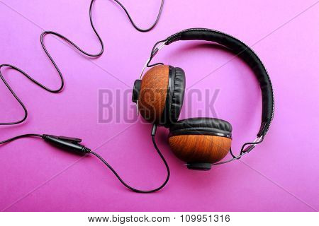 Black and brown headphones on purple background