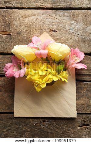 Fresh bouquet of flowers in envelope on wooden background