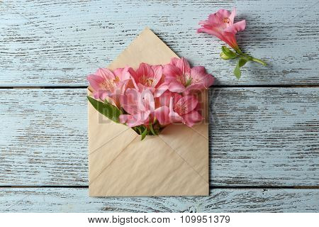 Pink alstroemeria in envelope on wooden background