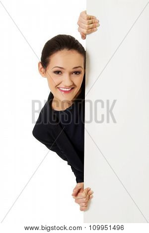 Young happy businesswoman holding empty banner.