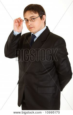 Elegant young businessman straightening eyeglasses