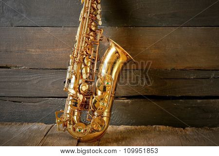 Beautiful golden saxophone on wooden background, close up