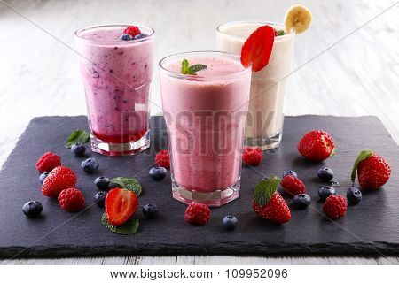 Milkshakes at cutting board with berries on light background