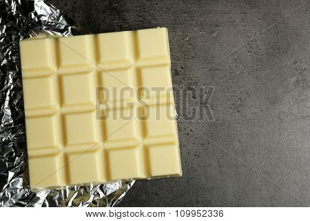 White Chocolate bar in foil  on gray background