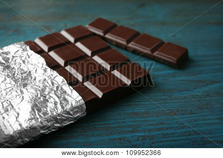 Dark Chocolate bar in foil  on gray background