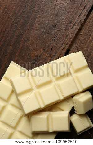 White chocolate pieces on wooden background