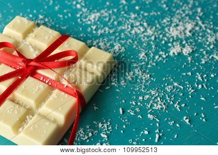 White chocolate bar with coconut shavings on color wooden background