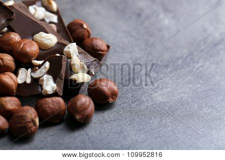 Black chocolate pieces and nuts on dark gray background
