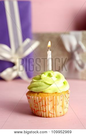 Tasty cupcake with candle on pink table against colourful present boxes background