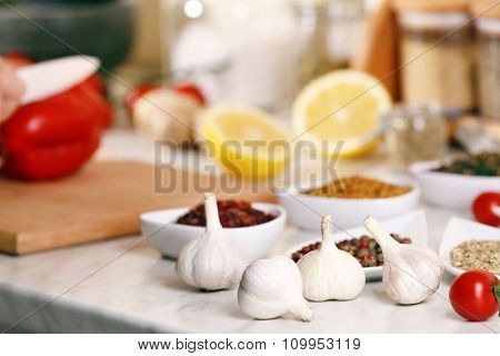 Garlic and variety of spices on the kitchen table